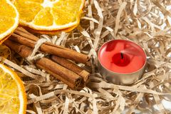Orange slice and fragrant cinnamon sticks with a red extinguished candle stock images