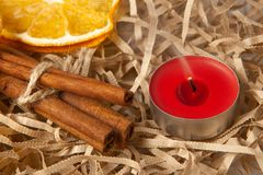 Orange slice and fragrant cinnamon sticks with a red extinguished candle, close-up royalty free stock image