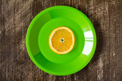 Orange slice in a green plate Stock Image