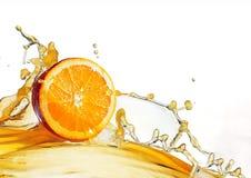 Orange slice in juice stream isolate on white.  stock image