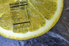 Orange slice with nutrition label on black Royalty Free Stock Photography
