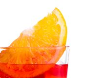 Orange slice on top of the red cocktail with ice cubes on white background Stock Photo