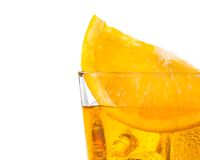 Orange slice on top of the yellow cocktail with ice cubes on white background Royalty Free Stock Photos