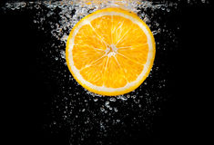 Orange slice in water with bubbles Stock Images