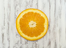 Orange slice. Overhead view on a white wooden kitchen table Royalty Free Stock Image