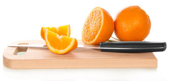 Orange sliced with knife on cutting board Stock Image