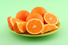 Orange slices. Fresh ripe orange slices on green plate and green background Stock Images