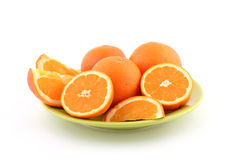 Orange slices. Fresh ripe orange slices on green plate isolated on white stock images