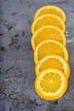 Orange slices arranged on a dark background Royalty Free Stock Images