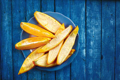 Orange Slices on Blue Wooden Board. Slices and peels of orange fruit on blue painted wooden board made of planks Royalty Free Stock Photos