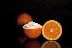 Orange Slices with Body Mask. Orange Slices with reflections and topped with orange body mask isolated on black Royalty Free Stock Photo