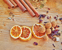 Orange slices, cinammon rolls and other spices and grains. Dried orange slices, cinammon rolls and other spices and grains on raw wooden table royalty free stock images