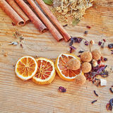 Orange slices, cinnamon rolls and other spices and grains. Dried orange slices, cinnamon rolls and other spices and grains on raw wooden table royalty free stock photos