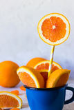 Orange slices in a cup. Fresh orange slices in blue enamel mug Royalty Free Stock Photography