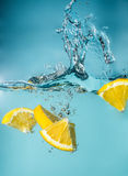 Orange slices falling into the blue water close-up, macro, splash water, bubbles,  blue background Stock Image