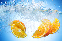 Orange Slices falling deeply under water with splash Royalty Free Stock Images