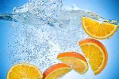 Orange Slices falling under water with splash Royalty Free Stock Images