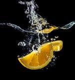 Orange slices falling into the water close-up, macro, splash, black background Stock Photo