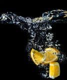 Orange slices falling into the water close-up, macro, splash, black background Stock Photography
