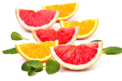Orange slices and grapefruit and mint leaves. Juicy ripe orange slices and grapefruit and mint leaves Royalty Free Stock Image
