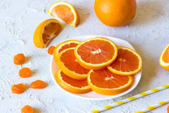 Orange slices on a plate. Three orange slices on a textural light gray background Stock Photography