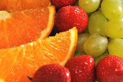 Orange slices with strawberries and grape. Closeup view on orange slices with strawberries and grapes stock photo
