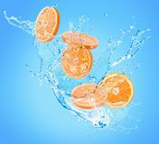 Orange slices in water splash on a blue background stock photography