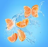 Orange slices in water splash on a blue background royalty free stock photos