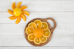 Orange slices are well decorated on cutting board with a lemon. Royalty Free Stock Photography