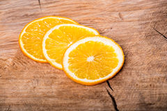 Orange slices on wooden board Royalty Free Stock Images