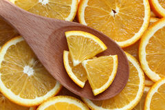 Orange slices in a wooden spoon. On orange slices background. Close-up Royalty Free Stock Images