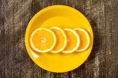 Orange slices in a yellow plate Royalty Free Stock Photo