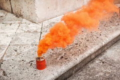 Orange smoke can on stony ground Stock Image