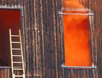Orange smoke comes out of the window and a ladder of the fire ne Stock Photo