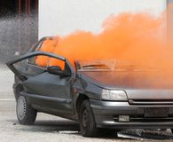 Orange smoke escapes from the car destroyed Stock Photo