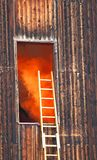 Orange smoke escapes from a wooden house during the fire Stock Photo