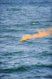 Orange smoke flare in the water. Orange smoke comes out from a flare fired during a safety demonstration drill on the sea stock image