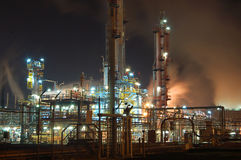 Orange smoke of industry. Petroleum Refinery by night with soft billowing clouds of orange smoke Stock Photos