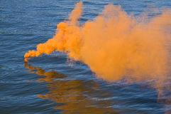Orange smoke on water Royalty Free Stock Image