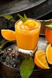 Orange smoothie and orange fruits with green leaves on dark back royalty free stock image