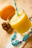 Orange smoothie in a glass. Beads and netsuke. Vertical shot Stock Photos