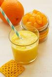 Orange smoothie in a glass. Candied kumquat. Stock Photos