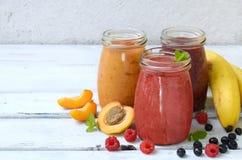 Orange, smoothies sains rouges et pourpres des ingrédients frais - bananes, abricots, framboises et myrtilles sur un backgrou lég Photographie stock