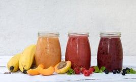 Orange, smoothies sains rouges et pourpres des ingrédients frais - bananes, abricots, framboises et myrtilles sur un backgrou lég Photo libre de droits