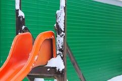 Orange snöig glidbana för ungar med grön bakgrund arkivbild