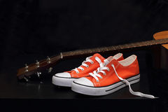 Orange sneakers and guitar Stock Photos