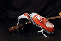 Orange sneakers and guitar Stock Images