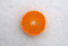 Orange on the snow. Half of orange on the snow Royalty Free Stock Photography