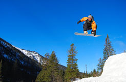 Orange snowboarder jumping high royalty free stock photo