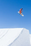 Orange Snowboarder Leaving Ramp. Snowboarder competing in competition in Val Thorens, France royalty free stock image